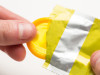 Hand pulling yellow condom from wrapper on white background