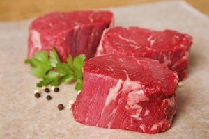three raw beef tenderlion steak fillets on resting on wax paper with flat leaf parsley and whoel black and white peppercorns